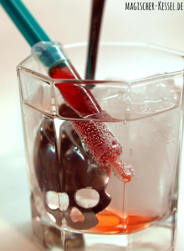 Blutiger Haloweencocktail mit Spritze und Erdbeersirup