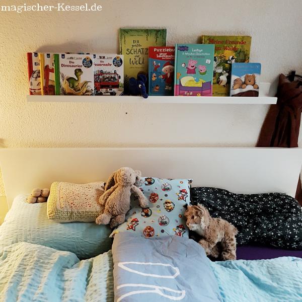 Familienbett mit Kinderbüchern und Kuscheltieren