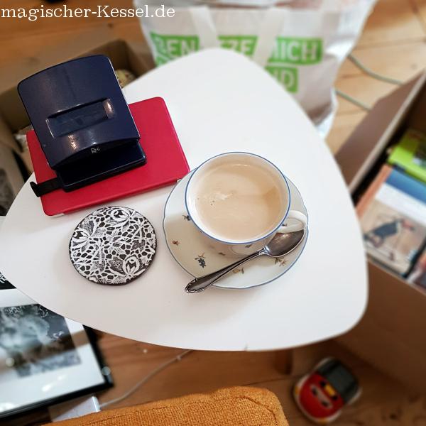 Beistelltisch mit Kaffeetasse voller Milchkaffee