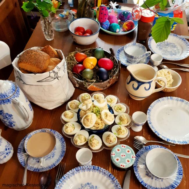 Gedeckte Tafel mit Osterfrühstück. Tellern, Tassen, Osternest, Brötchen, Osterstrauß