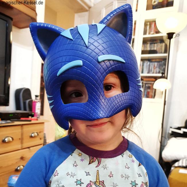 Kind mit PJ-Masks-Plastikmaske auf