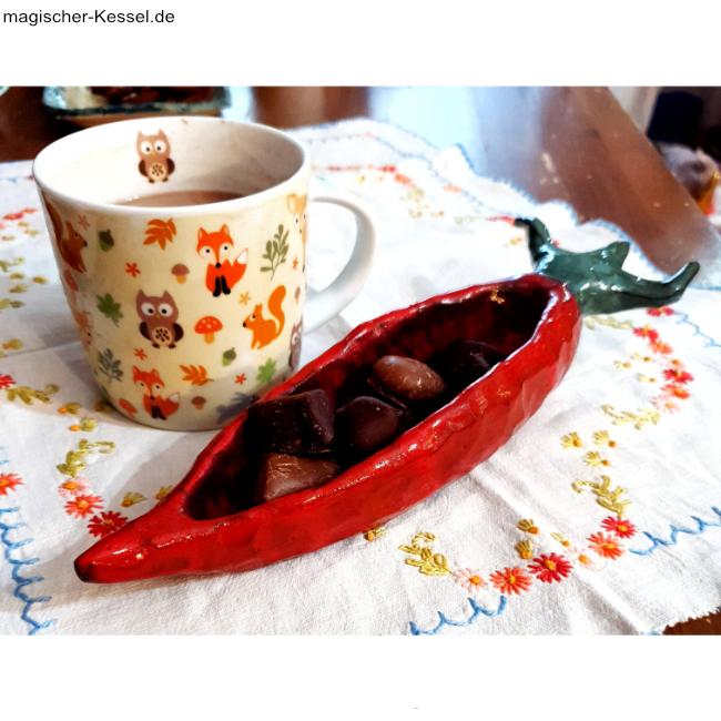 Bestickte Blumentischdecke. Darauf eine Kakaotasse und eine handgetöpferte Schale in Form einer Möhre, gefüllt mit Schokolade