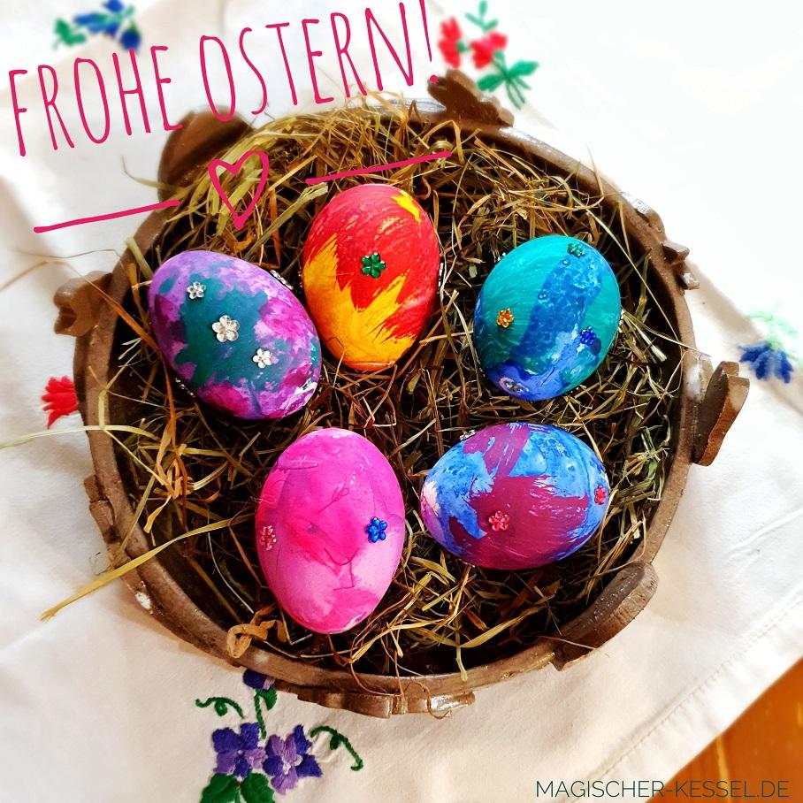 Osterteller mit von Kinderhand bemalten Eiern und Glitzeraufklebern